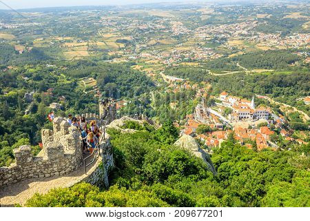 Sintra, Portugal - August 7, 2017: people tourists walking on the old walls of Castle of the Moors, the Moorish Medieval Fortress and UNESCO Heritage, and observing the Sintra National Palace on right