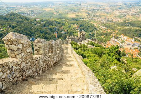 The ancient walls of ruins of Castle of the Moors. The Moorish fortress is a medieval castle and Unesco Heritage on top of a hill above Sintra, Portugal. On right aerial view of Sintra National Palace