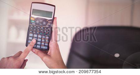Composite image of hands of businesswoman using calculator