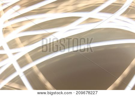 Bright Light Pattern Abstract Background. Shiny yellow white colored curved glowing lines. Soft blur bokeh simple pathway with empty copy space at the bottom of picture. Celebration wallpaper concept