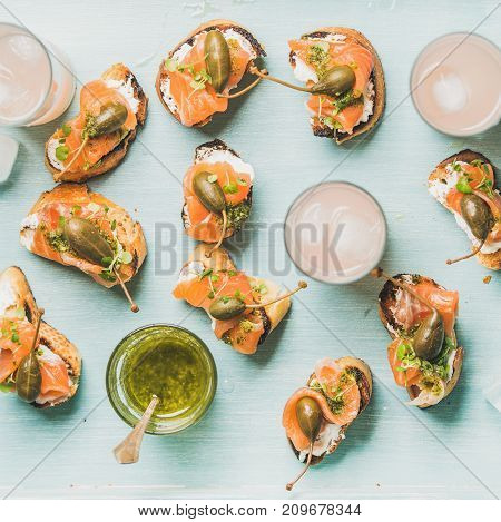 Crostini with smoked salmon, pesto sauce, watercress and capers and pink grapefruit cocktails over light blue background, flat-lay, top view, square crop. Party, catering or fingerfood concept