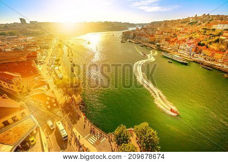 Aerial panoramic view of Oporto skyline and Ribeira Waterfront from Dom Luis I Bridge at twilight. Picturesque urban cityscape of Porto, Portugal. Tourist boats cruising on Douro River at sunset light