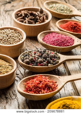 Assortment of colorful spices in the wooden spoons and bowls.