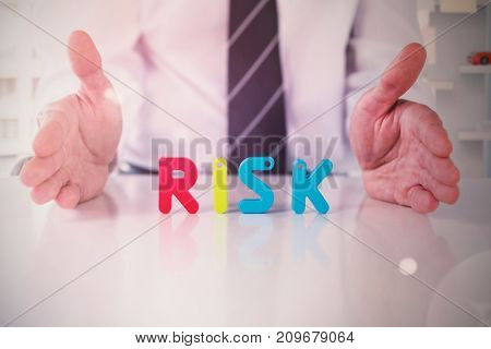 Mid section of businessman with colorful risk text against view of office interior with sticky note on window