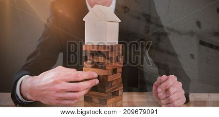 Businessman arranging blocks with model house on top against grey