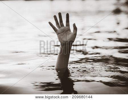 Drowning victims Black and white hand of drowning man needing help. Failure and rescue concept.