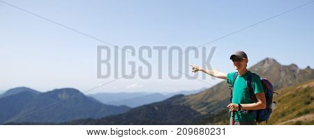 Image of tourist guy points away from scenic mountains