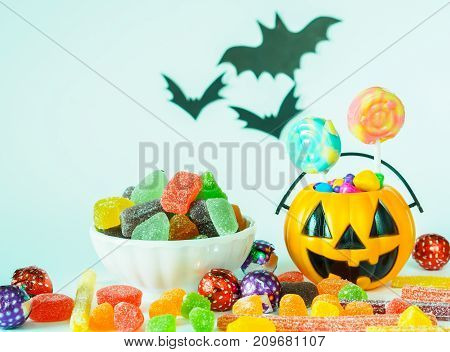 Trick or treat halloween bucket filled with colorful candies on white background