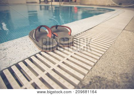 Orange slippers on the swimming pool background