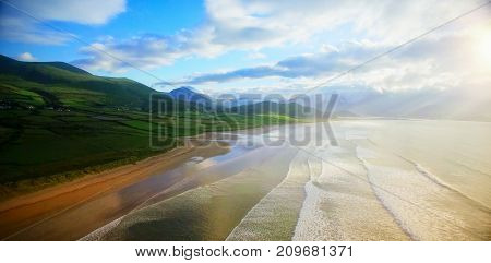 Idyllic view of mountain by sea against cloudy sky