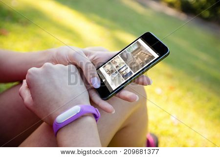Interior of bedroom on mobile screen against woman with fitness band on wrist using phone