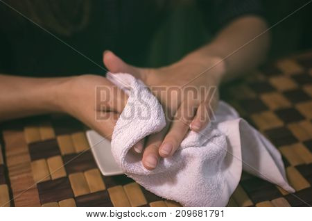 Young woman girl sitting at the table in cafe and wiping her hands with a wet towel and preparing to eat sushi.
