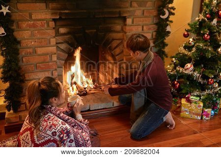Young couple spending Christmas night at firepalce at home