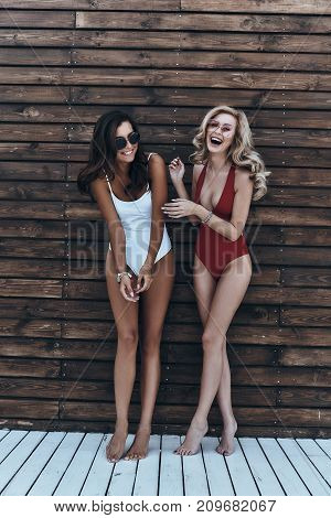 Having fun together. Full length of two attractive young women in swimwear laughing while standing against the wooden wall outdoors