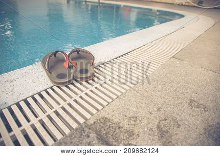 Slippers and swimming pool in a summer day