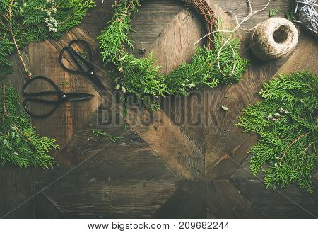 Preparing for Christmas or New Year holiday. Flat-lay of fur tree branches, evergreen wreaths, rope, scissors over rustic wooden table background, top view, copy space, horizontal composition