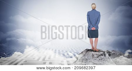 Businesswoman standing with hands behind back against maze ending in cloudy sky