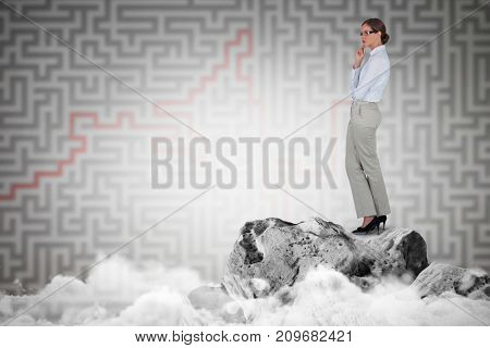 Thoughtful businesswoman standing  against grey maze