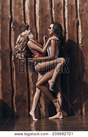 So much fun together. Full length of two playful young women in swimwear embracing and smiling while posing against the wooden wall outdoors