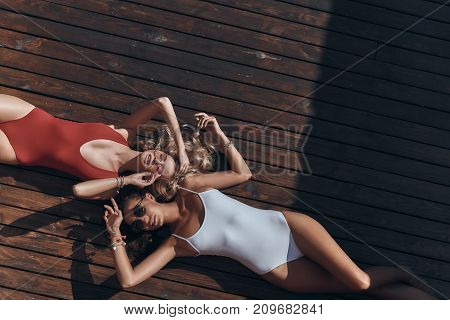 Summer relaxation. Top view of two attractive young women in swimwear smiling while lying down on the wooden floor together
