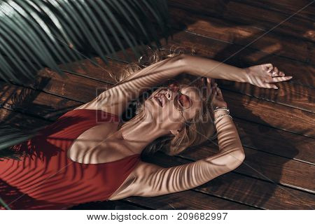 Total relaxation. Top view of beautiful young woman in swimwear keeping eyes closed and mouth open while lying under the palm tree poster