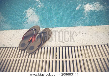 Pair of orange slippers beside the swimming pool
