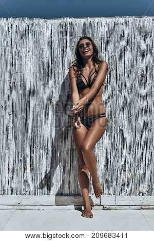 This summer is hot! Full length of attractive young woman in swimwear laughing while standing outdoors