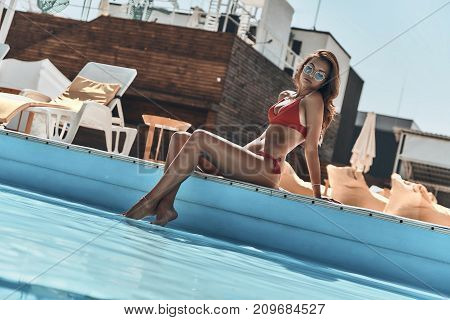 Enjoying hot summer day. Beautiful young woman in swimwear resting while sitting by the pool outdoors