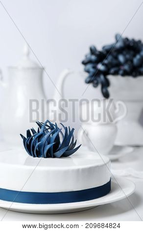 Holiday white mousse cake decorated with blue creative flower with tea set and grape on stand cake on background. Vertical Food Drink Concept. Wedding classic pastry in restaurant. Celebrating Sweet