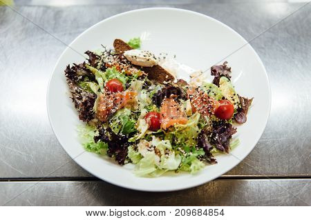 Caesar salad in a white plate on a metal surface.