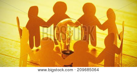 High angle view of blue paper figures standing around light bulb on wooden table