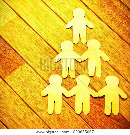 High angle view of paper cut out figures forming human pyramid on wooden table