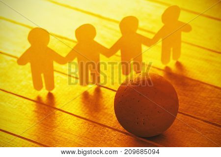 High angle view of paper cut out human chain by ball on wooden table
