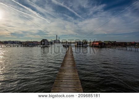 Lake Bokod with pier and fishing wooden cottages, power plant in background, Hungary