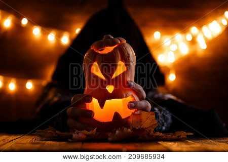 Picture of halloween pumpkin cut in shape of face with witch on background with burning yellow lights