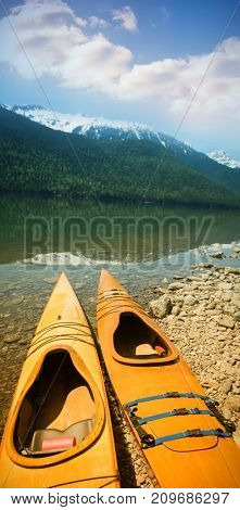 Kayaks at lakeshore against mountain on sunny day