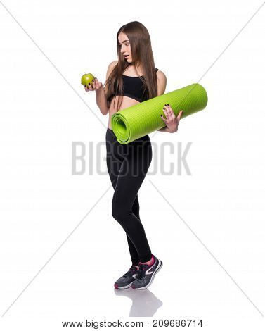 Portrait Of Smiling Young Woman Holding Rolled Up Exercise Yoga Mat And Green Apple Isolated On Whit