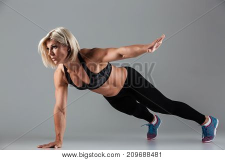Full length portrait of a concentrated muscular adult sportswoman doing push-ups with one hand isolated over gray background