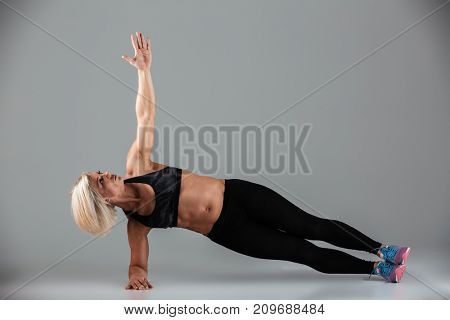 Full length portrait of a focused muscular adult woman doing plank exercise with on hand isolated over gray background