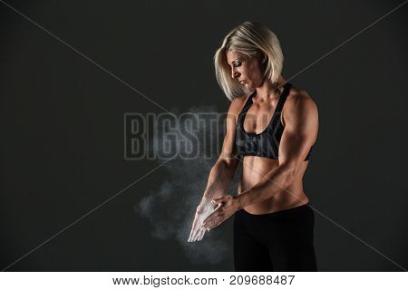 Portrait of a muscular sportswoman clapping hands with talc powder before doing excercise isolated over gray background