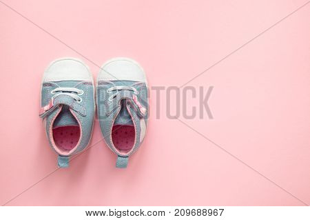 Children's denim sports shoes for girls, stands on a pink background. closeup view from the top. the concept of children's clothing.