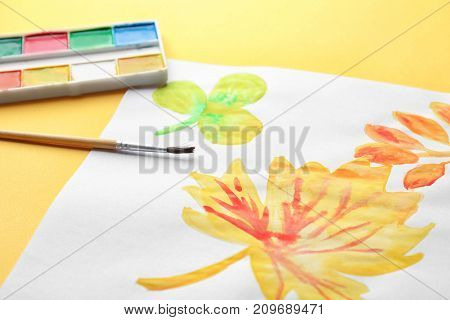 Child's painting of autumn leaves on color background, closeup