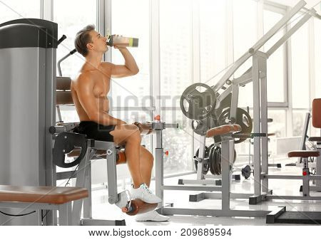 Sporty young man drinking protein shake in gym