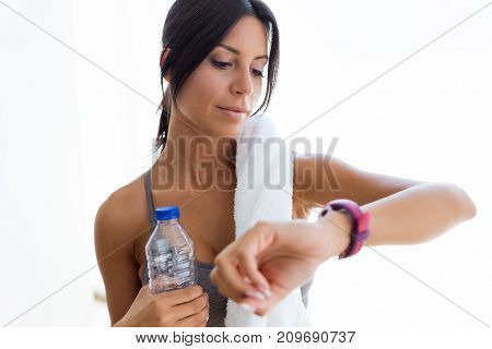 Beautiful Young Sporty Woman Looking Her Smartwatch At Home.