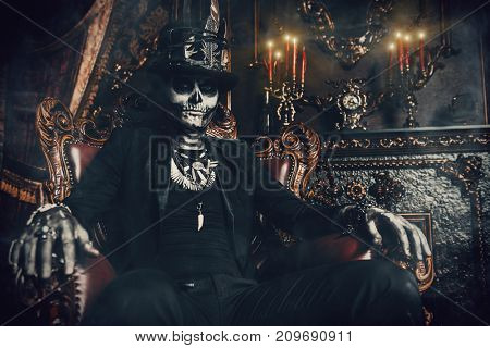 Halloween. A man with a skull makeup dressed in a tail-coat and a top-hat is in the old castle. Baron Saturday. Dia de los muertos. Day of The Dead. Old vintage interior.