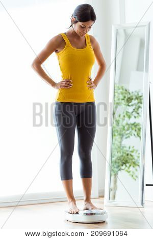 Beautiful Young Healthy Woman On Home Scales.
