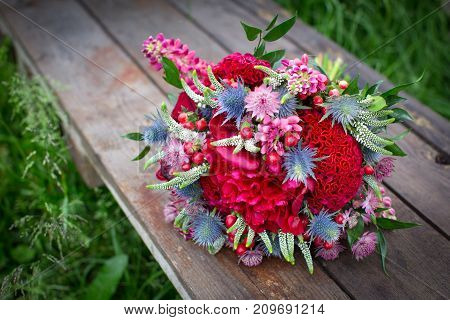 Bridal bouquet in rustic style lying on the stump outdoors. wedding concept