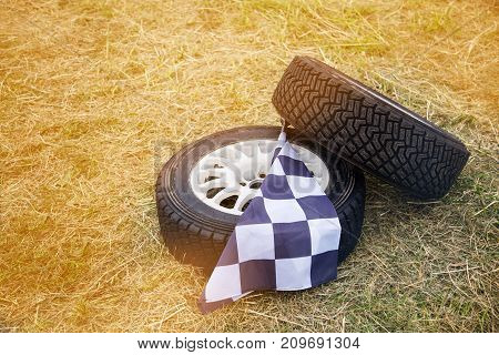 two wheels and the finish flag on the grass closeup . changing the wheels. the winner of the race. the concept of the car