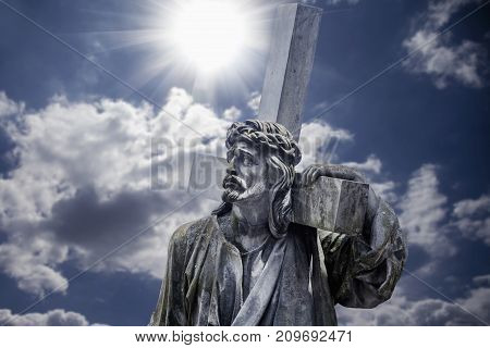 The road to Golgotha. Ancient statue of Jesus Christ with cross. (holy faith religion God suffering concept)