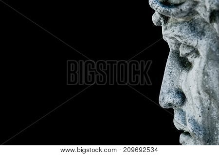 An ancient statue of the crucifixion of Jesus Christ in profile (religion faith death suffering immortality God concept)